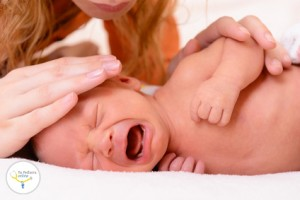 mothercare, young mother calms her newborn baby during she is cr