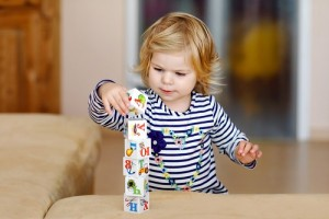 Adorable toddler girl playing with educational toys in nursery. Happy healthy child having fun with colorful different plastic blocks at home. Cute baby learning creating and building