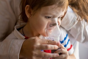 Young woman with son doing inhalation a nebulizer at home